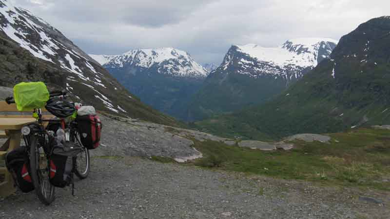 touring bike next to a bench with Norwegian mountains behind